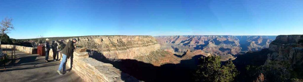People stand behind a wall to safely view the Grand Canyon