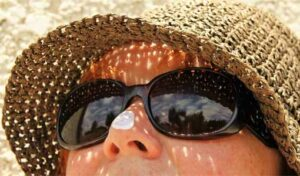 A woman wears a sunhat, sunglasses, and sunscreen