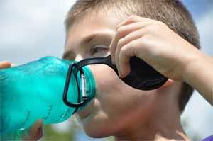 A boy drinks water from a water bottle